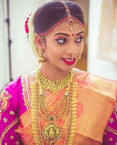 South Indian bride. Gold Indian bridal jewelry.Temple jewelry. Jhumkis. Orange silk kanchipuram sari with contrast pink blouse.braid with fresh jasmine flowers. Tamil bride. Telugu bride. Kannada bride. Hindu bride. Malayalee bride.Kerala bride.South Indian wedding.