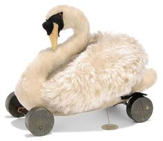 A STEIFF ARCHIVE MOHAIR SWAN ON WHEELS, (2322), white, black boot button eyes, red disc behind, black and yellow felt beak and face mask, black feet, ribbed felt backs of wings forming an arch, on green eccentric wooden wheels and Steiff Archive handwritten card tag 'Schwan 2322 21 1919 - Ind, 8276 B105', circa 1919 --11½in. (30.5cm.) long