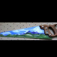 I painted this years ago.  Pretty mountains, trees and a grassy pond on a neat old hand saw.