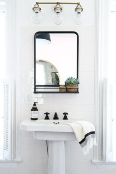 white & black bathroom with pedastol sink and black framed mirror