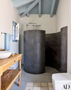 In a Greek home designed by Isabel López-Quesada, the poolhouse's coiling shower enclosure is fashioned of tadelakt, a waterproof Moroccan plaster; the showerhead is by Grohe.