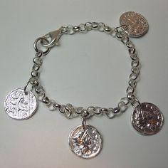 Pulsera de plata de ley con cadena rolo y monedas romanas terminada en brillo con cierre mosqueton.