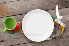 Plate with measure tape, cup, knife and fork. Diet food ...  above, background, care, centimeter, clean, concept, conceptual, copy, copyspace, cup, diet, dieting, dining, dish, dishware, drink, eat, fat, fitness, food, fork, health, healthy, heart, kitchen, knife, life, lifestyle, loss, lunch, meal, measure, measurement, measuring, meter, plate, slim, space, table, tape, top, water, weight, white