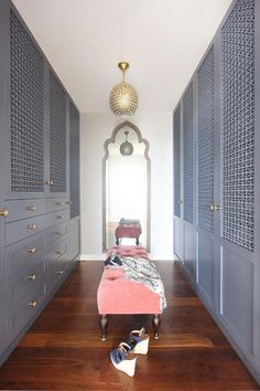 Jenny Wolf - Amazing gray walk-in closet features floor to ceiling gray mashrabiya style cabinets adorned with moter of pearl knobs by Anthropologie. A closet accent wall is clad in Serena & Lily Lamu Wallpaper lined with a gray Moroccan mirror placed behind a salmon pink velvet tufted bench illuminated by a Serena & Lily Marmont Pendant.