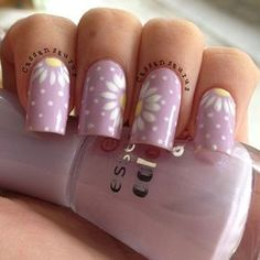 Floral and polka dot inspired Purple nail art design. You can see flowers on each nails that are surrounded by white polka dots which makes the entire design look adorable.