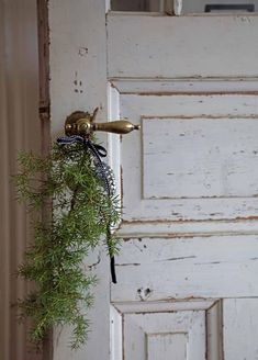 somthing so simple like hanging a piece of evergreen on a doorknob looks so festive