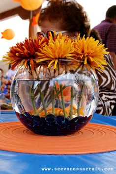 Live fish made for  super cheap centerpieces and I'm happy to say that no fish were harmed during this party. I added blue glass beads and artificial flowers to the bowl. Whoever wanted a fish bowl at the end of the party took home a new pet with baggies of fish food and care instructions.