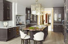 """Burberry-Inspired   Since you can look right into the kitchen from the front door of this 1909 Beaux Arts townhouse, it had to live up to its surroundings. """"White never came into my head,"""" says designer Christopher Peacock. """"It was more about dark, masculine colors."""" When Peacock walked into the AKDO tile showroom and saw their new Balmoral Plaid pattern, he immediately thought of a classic Burberry raincoat. It fit right in with the tailored look he was after. LOVE THE LOOK"""