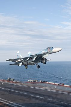 """""""Sukhoi Su-33 Flanker-D Fighter Jet flying above the Admiral Kuznetsov Aircraft Carrier."""""""