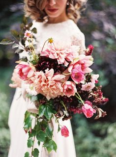 Bows + Arrows surrounded oversized dahlias with pink lilies, tulips, and small burgundy sprouts for depth;cascading ivy gave the bouquet an elongated look.