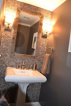 Powder room tiled wall with homemade mirror frame.