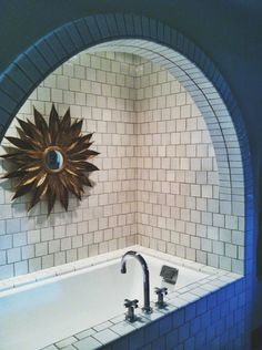 Exquisite bathroom features arched bathtub alcove accented with white square tiles and adorned with gold sunflower mirror. Bathroom tub sunburst mirror