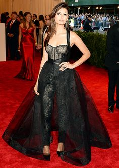 Nina Dobrev at the Met Gala in a custom Monique Lhuillier black Chantilly lace molded bustier jumpsuit with black leather harness tulle overskirt with horsehair trim.