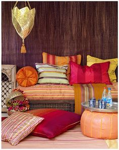 Orange, Pink and Yellow Pillows and Couch. Moroccan influenced interior design. The warm colors are nice during northern winters.
