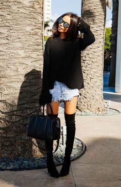 Street style look suéter preto, shorts jeans, bota over the knee e bolsa preta.