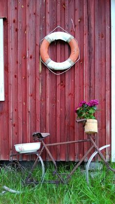 Cottage decor made with a rustic, old bike, porcelain bowl, flowers and a life buoy