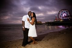 Beautiful engagement photo with the lights of a ferris wheel in the distance. Photo by The Visual Artist Studios - San Bernardino, CA Wedding Photographer | SnapKnot