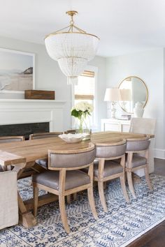 Rug under the dining room table is a must. This is pretty perfect if you get rid of the gaudy chandelier and stuffy sideboard vignette.