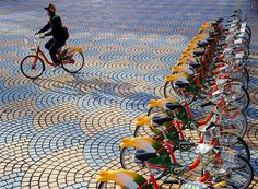 A woman rides a bike-share bike past a renting station outside Taipei City Hall in Taiwan.