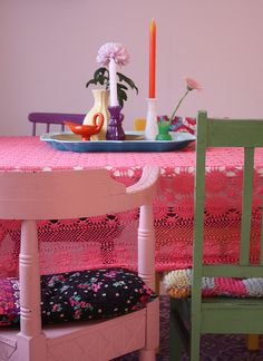 Colorful dining table and chairs -- I especially like the bright doily tablecloth!