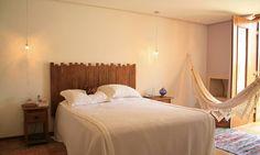 Estilo rústico no quarto do casal, com cabeceira e mesinha lateral de madeira de demolição e rede de crochê. A bossa fica por conta das luminárias pendentes Divulgação