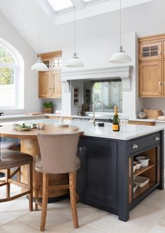 here is an example of a charcoal island with wood cabinets and white walls and ceiling. I think you can imagine the granite you already have on the island. A charcoal sofa in a nubby, tweed fabric, or wide wale corduroy, with that wood chair and ottoman with matching cushions... the saddle leather chairs, light grey or white walls white ceilings.
