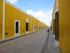 A street lined with yellow painted buildings in Izamal, Yucatan, Mexico -> Check out my blog post for more photos of Izamal along with my detailed guide and stories from my experiences exploring there!