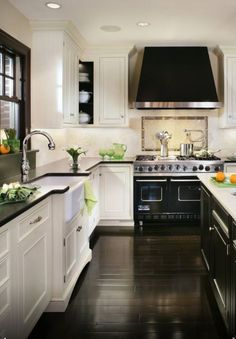 dark wood floors, white cabinets, dark grey/black counter tops.  love the black hood too