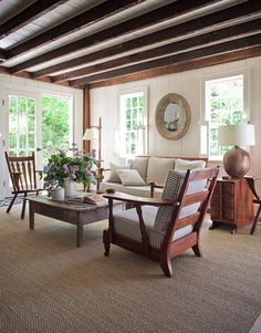 "Living Room  Rustic and refined: designer Shawn Henderson's updated colonial farmhouse in Hillsdale, New York. In the living room, he mixed vintage rock maple Cushman furniture with weathered pine pieces and painted the wood walls Benjamin Moore's Sail Cloth. ""I tried to echo the graphic aspect of the ceiling beams with the brown and white ticking on the cushions,"" he says."
