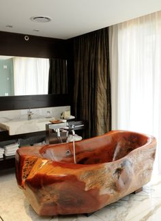 Argentine artist Mario Dasso hand-carved each bathtub from a single piece of native calden wood, using trees already felled by natural occurrence.