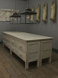 Upon the wall is a set of papier mache butcher's shop props and a detailed fragment from Marske Hall, Marske-by-the-Sea.    Above the C20th painted sideboards are two bespoke 'Galley Lanterns' with an aged copper finish.