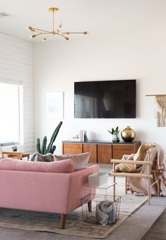 Midcentury inspired living room design with plenty of brass and pops of pink.