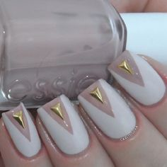 Beautiful white and gold nail art design. The nails are designed with the white polish forming a v-like shape on the edge of the nails and the gold is used as an embellishment on top of the nails.
