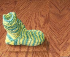 This pattern is a triple whammy. First it's the ideal for that little bit of sock yarn you have left over from the adult socks. Second it's sure to be a hit at any baby shower, as all the guests ooh and ahh over the cuteness of baby socks. And lastly, the baby will have toasty tootsies! Using a two color sock yarn will cause stripes due to the tiny sized foot.