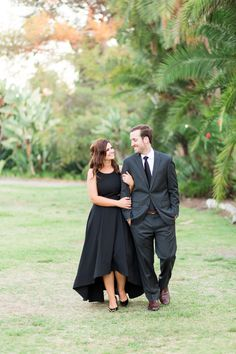 Couple walking together in a high low black formal gown by Aidan by Aidan Mattox @AidanbyAM and a suit and tie for San Diego engagement photos, Chis modern and sophisticated engagement photos, Cavin Elizabeth Photography