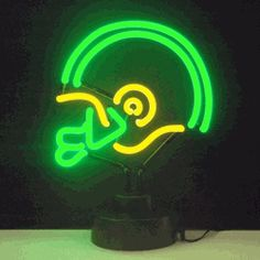 "GREEN AND YELLOW FOOTBALL HELMET NEON SCULPTURE-NN4GYHEL  12"" wide, 12"" high, 6"" deep  Guide your friends to the place to catch the game with a Green/Yellow Football Helmet Neon Sculpture, constructed of hand blown neon tubing fitted into a black base. The Green/Yellow Football Helmet Neon Sculpture measures 12"" wide, 12"" high, and 6"" deep. It is adaptable to hang on the wall or sit on a flat surface and features an on/off switch on the base."