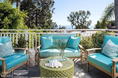 Chic patio features a teak sofa and chairs lined with turquoise blue cushions lined with turquoise border pillows and turquoise diamond pillows facing a round green metal lattice outdoor coffee table painted lime green.