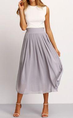 Ella llevando un vestido gris y blanco con tacones altos. El vestido y tacones altos cuesta quienitos pesos.