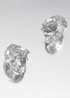 PAIR OF DIAMOND EARRINGS, GRAFF.  Each designed as a stylised hoop dressing the ear, set throughout with step-cut diamonds, clip fittings, signed Graff.