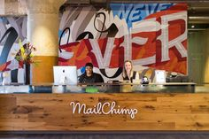 "MailChimp's Atlanta office reception desk is backed by a mural that reads ""Passion Never Fails""by the Brooklyn-based artist known as Never."