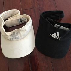 Two Adidas visors Two adidas visors. White has been worn more than black so some discoloration. Adidas Accessories Hats