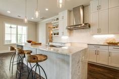 Contemporary Kitchen with Pendant light, Complex marble counters, Shades of light glass jug pendant light, Subway Tile, Flush