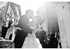 Reportaje fotográfico Fotografía en blanco y negro donde los novios se besan con el único testigo de los invitados y una bella y radiante lu...