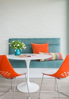 breakfast nook with white tulip table, blue bench, and orange chairs