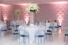 Blush uplighting by Skm Entertainment. Blush Lamour napkins with white dining table linens for wedding reception at The Clayton on the Park. Centerpiece by Flora Bella. Photographer Ryan Nicole Photography. #white #blush #wedding #reception #ideas #modern #elegant #classic #uplighting