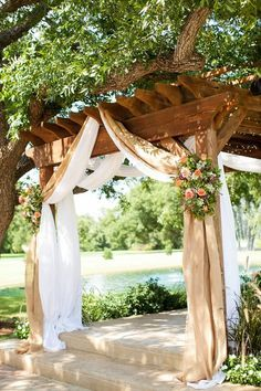 Burlap draping with country pink and green flowers over a wooden pergola…