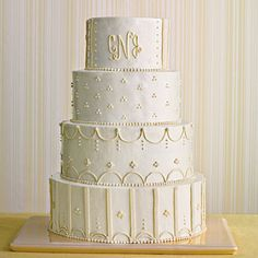 Monogrammed Wedding Cake | Go with an old Southern favorite and monogram your cake with the bride and groom's initials. Dressed in ivory and white, the look is updated by skipping a topper.
