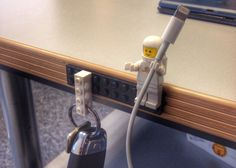 Who knew that LEGO designed their figures' hands perfectly to hold Apple lightning and other types of cables? Stick a LEGO brick on your desk, attach LEGO figure(s), and, voilà, an ingenious cord-catching solution.