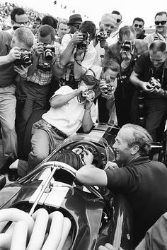 1965 Indy 500. The genius behind all things Lotus, Colin Chapman next to the car, with Jimmy Clark in the car.