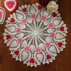 A beautiful Valentines Day decor! This exquisite heart doily is hand crafted. It is measured about 20 inches in diameter. It has a 10 pink hearts motifs and 10 red ones around it. The heart motifs are removable and use the doily itself during the non holidays. Lightly starched.